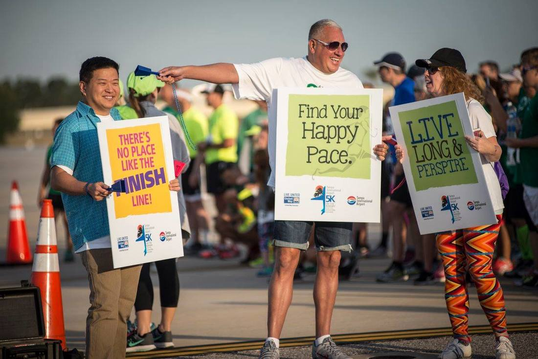 Volunteers hold motivational signs and cheer for runners at the 5K on the Runway.