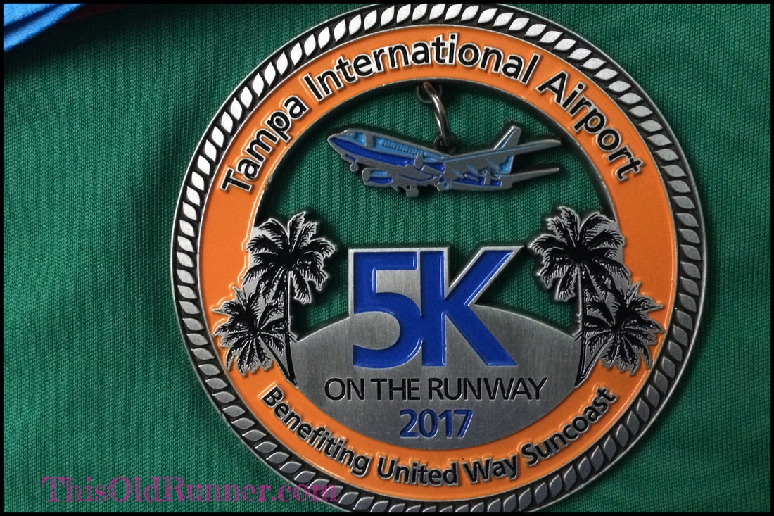 2017 medal for the TIA 5K on the Runway race has a moving plane.