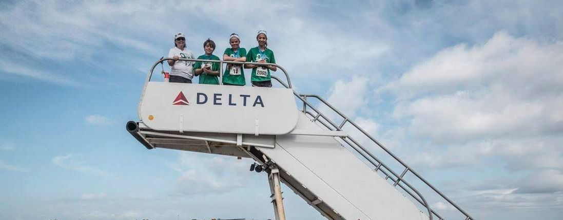 Runners pose on Delta airline steps at 5K on the Runway race in Tampa.