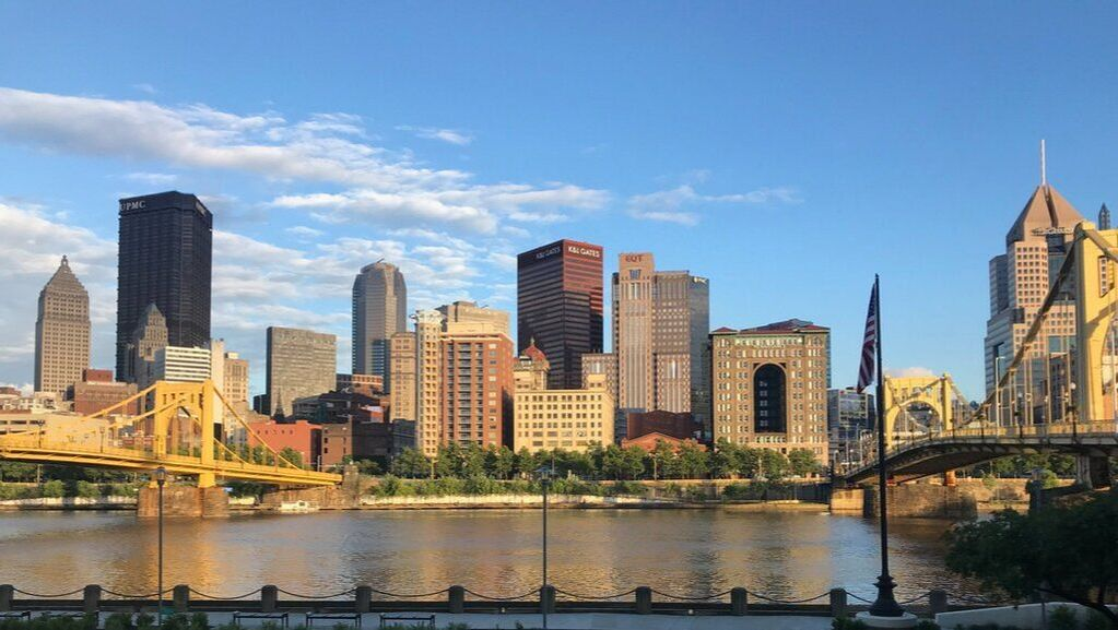 Picture of downtown Pittsburgh showing the river, two bridges and downtown office buildings.