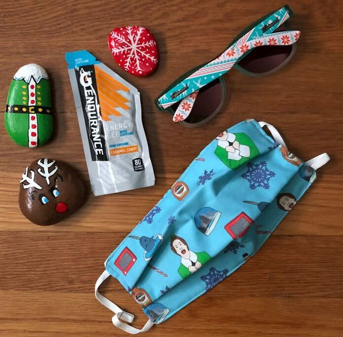 Painted holiday rocks, Gatorade Endurance energy gel, Elf mask and pair of Knockaround sunglasses in Ugly Sweater pattern.