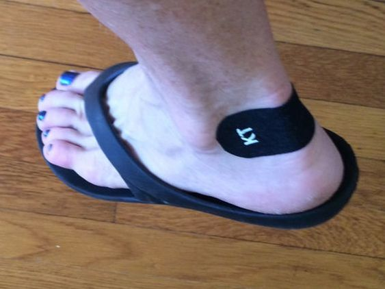 KT Tape on heel of foot in flip flop.