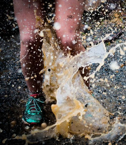 runner splashing in puddle