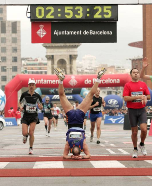 Runner does hand stand at finish line of race.