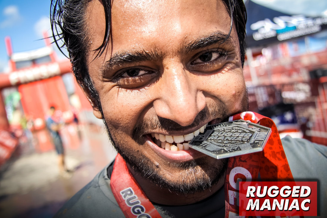 Man biting finisher medal at Rugged Maniac race finish line.