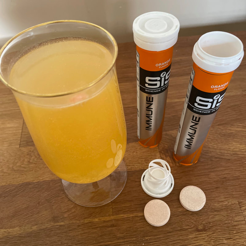 Glass of dissolved immunity tablet next to two tubes of Science in Sport immune tablets.