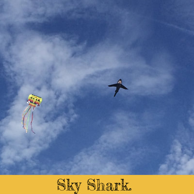 Shark and octopus kites in sky over the beach.