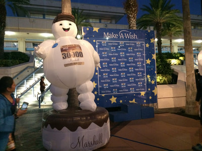 Marshall the Hot Chocolate Race mascot next to the Make A Wish donation station.