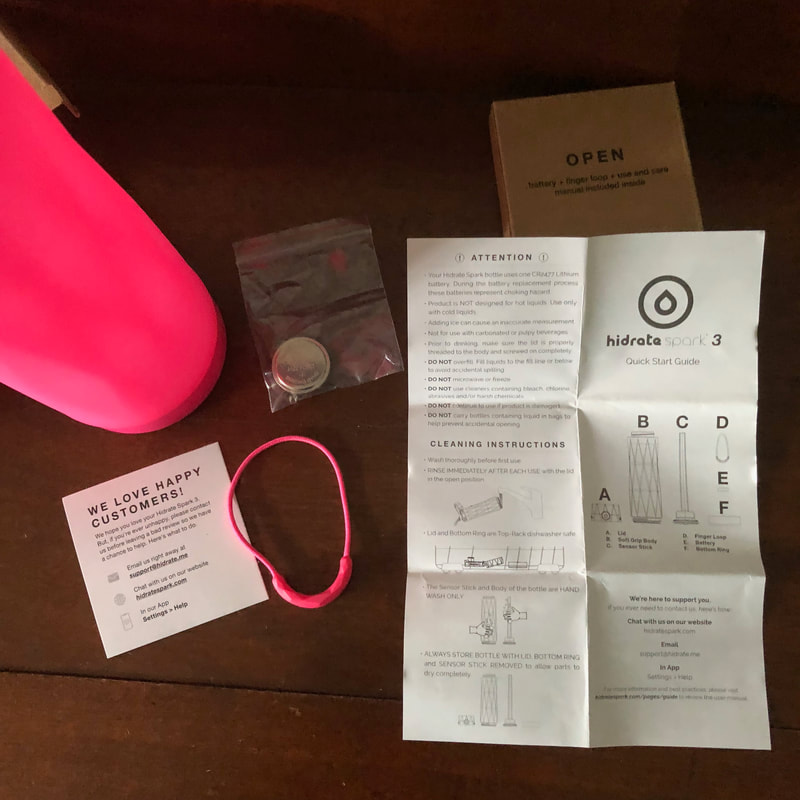 Unboxing Hidrate Spark 3 water bottle with finger loop, battery, and instructions.