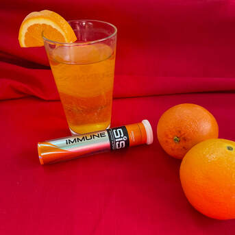 Tube of Science in Sport tablets next to glass of drink and two oranges.