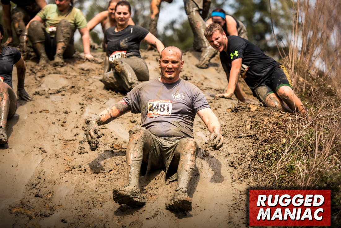 Rugged Maniac racers slide down a muddy hill.