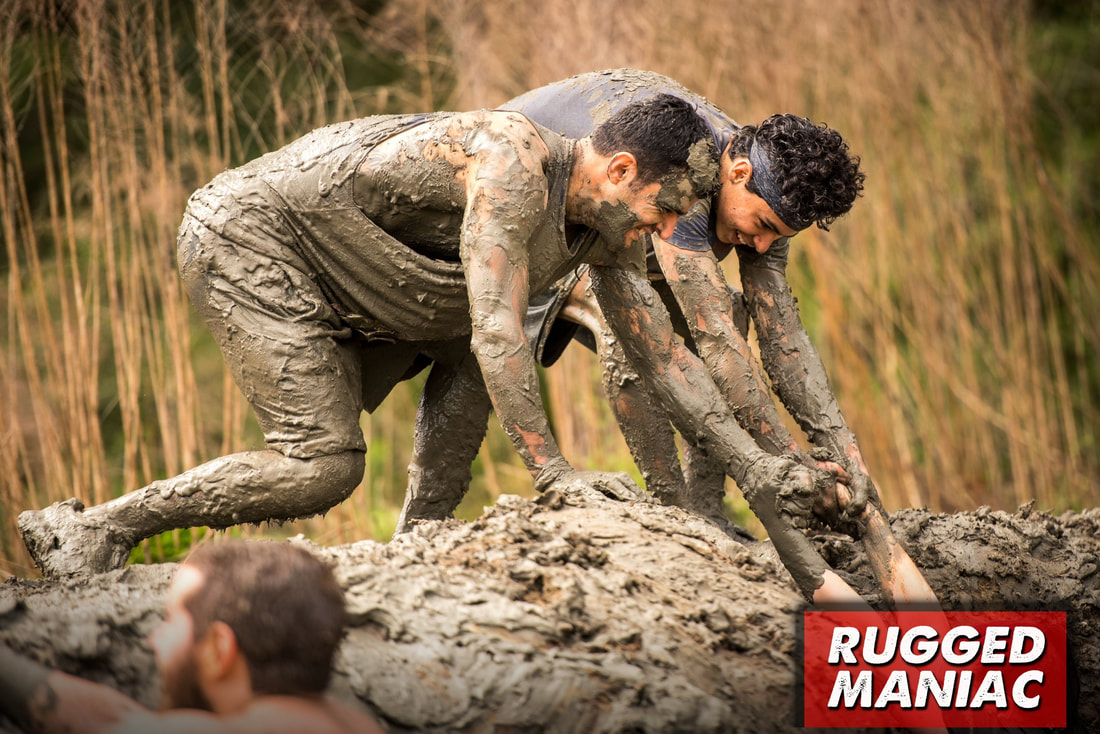 Two guys covered in mud assist another runner at the Rugged Maniac race.