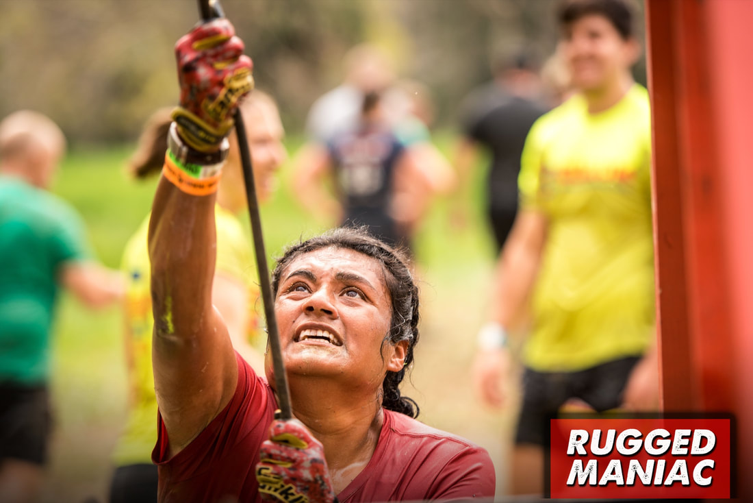Woman wearing gloves for obstacle at Rugged Maniac Mud Run.